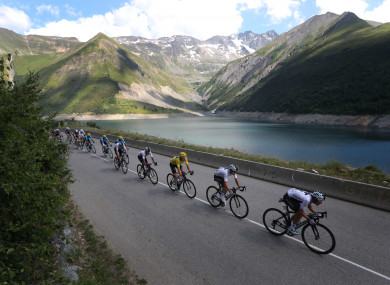 The pack with Britain's Geraint Thomas, wearing the overall leader's yellow jersey speeds down Croix de Fer pass.