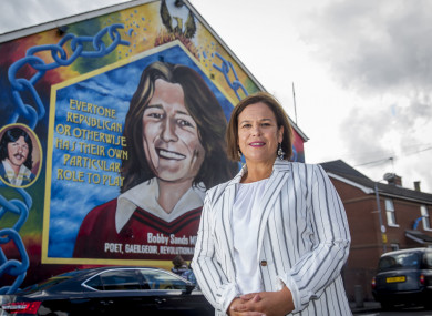 McDonald on front of a mural of Bobby Sands on the Falls Road in Belfast.