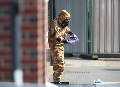 An investigator in a chemical suit removes an item as they work behind screens erected in Rollestone Street, Salisbury