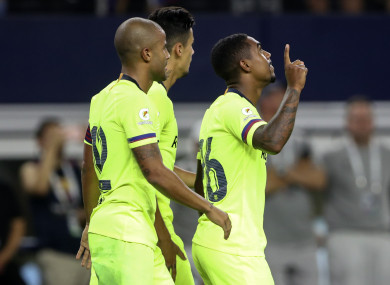 Malcom (right) celebrates his goal.