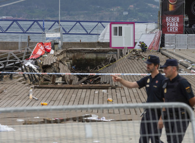 Two police officers walk at the scene the day after an oceanside boardwalk collapsed, in Vigo.