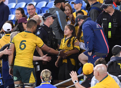 Lukhan Tui of the Wallabies (left) assists a family member after an altercation between Tui and a spectator.