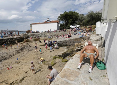 Members of the public relax while sunbathing at the beach at Sandycove during the summer heatwave.