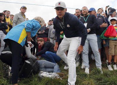 Brooks Koepka of the US offers a golf glove to a spectator he injured when his ball hit her on the 6th hole during his fourball match on the opening day of the 42nd Ryder Cup.
