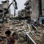 Palestinians clear rubble from the building housing the Hamas-run television station al-Aqsa TV.<span class=