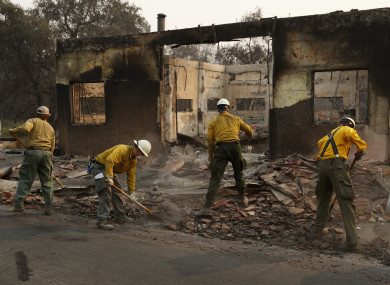 Fire crews clear rubble from the road near a building in Paradise, California.