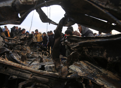 Palestinians inspect the remains of a destroyed vehicle.