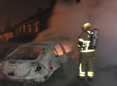 Firefighter in breathing apparatus extinguishing a car fire in South Dublin on Halloween.