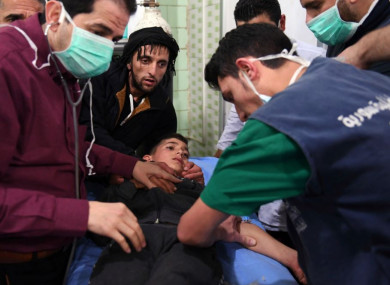 Medical staff treating a boy following a suspected chemical attack on his town of al-Khalidiya, in Aleppo.