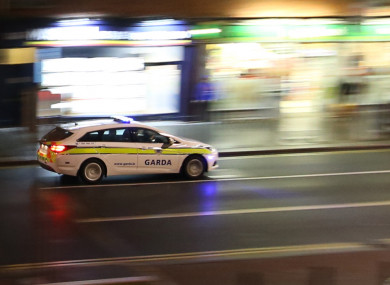 A Garda car speeds past the Phibsboro Tower in Dublin.
