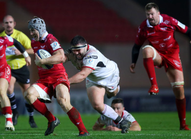 Moore strives to make a tackle against Scarlets.