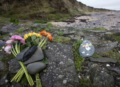 Flowers and a stone painted with the image of an angel near the location of where the baby's body was discovered.