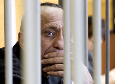 Mikhail Popkov looks through bars during a court session in Irkutsk, Russia