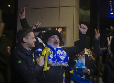 A Boca Juniors fan dressed as Maradona cheers outside the team's hotel in Madrid.