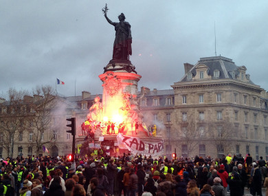 French anti-government protestors set alight a flare on the statue of Marianne, symbol of the Republic, in Paris, 8 December.