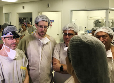 Dr Wellington Andraus, left with magnifying glasses, he and Dr. Dani Ejzenberg, second left, confer with colleagues at the Hospital das Clinicas of the University of Sao Paulo School of Medicine