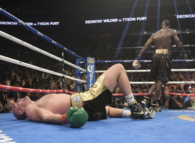 Deontay Wilder celebrates after knocking down Tyson Fury with a vicious two-punch combination.