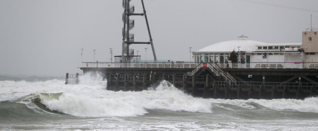 Waves crash against the pier in Bournemouth, United Kingdom.