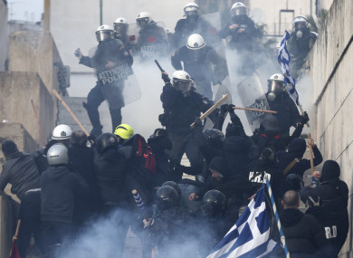 Demonstrators clash with Greek riot police after a rally in Athens