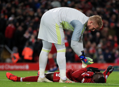 Liverpool's Naby Keita is checked on by Leicester City goalkeeper Kasper Schmeichel.