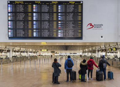 Passengers stand in a deserted departure hall at Brussels Airport in Zaventem, today.