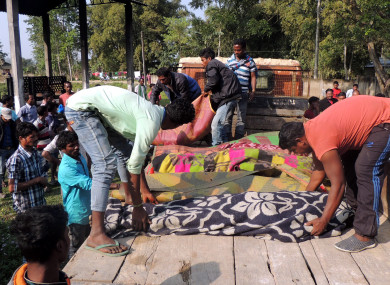 Locals arrange bodies of victims who died of consuming liquor.