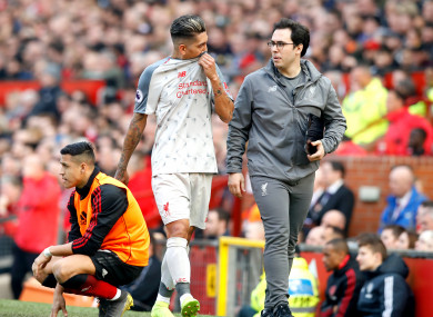 Roberto Firmino limps away from Sunday's draw at Old Trafford.