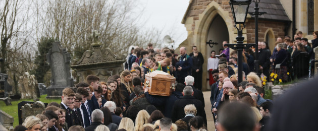 Mourners carry the coffin of Conor Currie into in Saint Malachy's Church, Edendork.