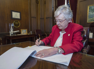 This photograph released by the state shows Alabama Governor Kay Ivey signing a bill that virtually outlaws abortion in the state
