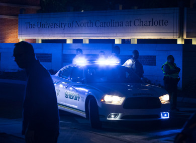 Police secure the main entrance to UNC Charlotte after a shooting incident at the school that left at least two people dead