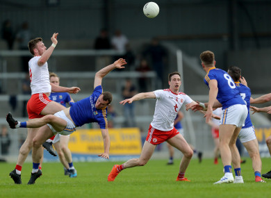 Tyrone's Brian Kennedy and David McGivney of Longford contest a high ball .