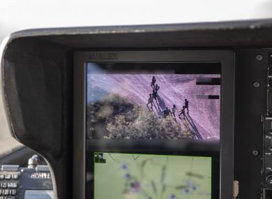 US Border Patrol agents watching Central American migrants who crossed the Rio Grande River from Mexico illegally on the camera of a search helicopter.