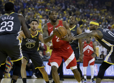 Kawhi Leonard looks to pass between Draymond Green and guard Klay Thompson.
