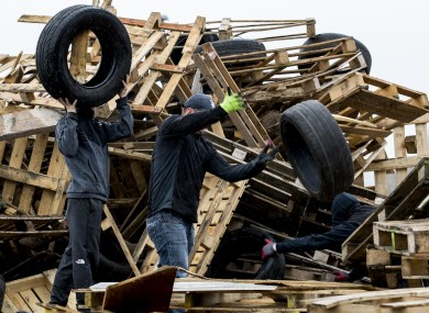 Men remove tyres from a July 11th night bonfire at Avoniel Leisure Centre yesterday