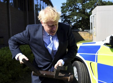 Boris Johnson  holds a battering ram during campaigning.