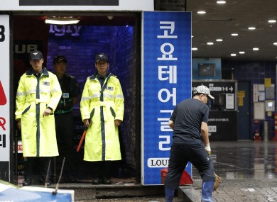 Police stand at the doorway to a nightclub in Gwangju, South Korea