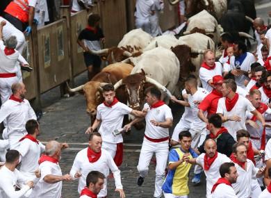Bulls un down a street during the traditional San Fermin bull run in Pamplona.