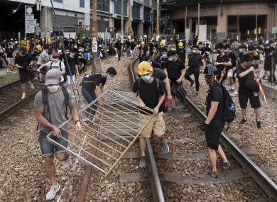 Protesters carry metal fences to be used as barricades during yesterday's protest in Yuen Long.