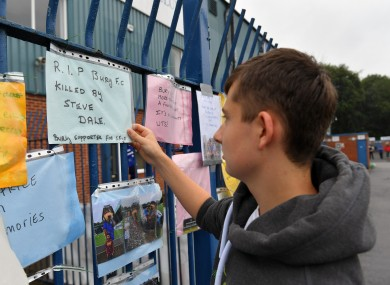 Messages from supporters are placed on a fence outside Gigg Lane stadium.