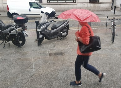 After weeks of good weather, today's sudden downpour sent Dublin residents running for cover. Pictured are pedestrians with umbrellas braving the wet weather.