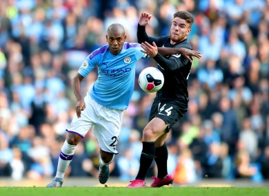 Aaron Connolly and Fernandinho battle for the ball.