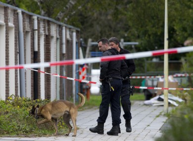 Forensic experts search for evidence in the area where a lawyer who represented a key witness in a major Dutch organised crime trial was gunned down in Amsterdam.