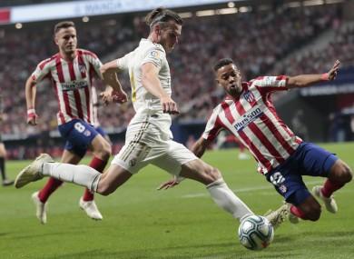 Renan Lodi blocks a pass by Real Madrid's Gareth Bale.
