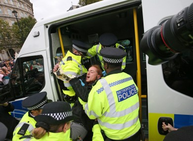 Police remove a protester from the Extinction Rebellion protest in Trafalgar Square in London