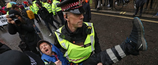An Extension Rebellion protester is carried away as others continue to block the road outside Mansion House in London.