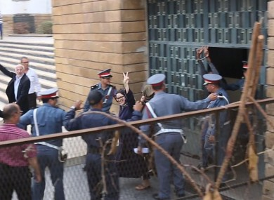 Raissouni gestures to supporters as she leaves a courtroom