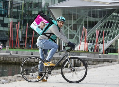 A Deliveroo rider with a bag showing an image of Trevor Deely, 22, who was last seen in Dublin in 2000