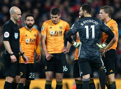 Wolves players and referee Anthony Taylor await a VAR review at Anfield.