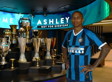 Ashley Young poses in an Inter shirt.