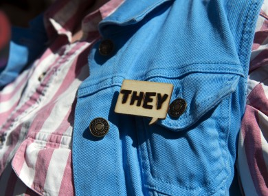 A person with a 'They' pin at a transgender community march in the US in October 2018.